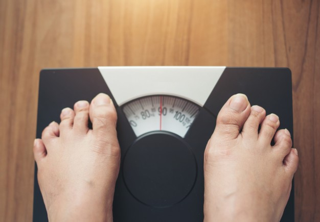 a person is weighing themselves on a weight scale