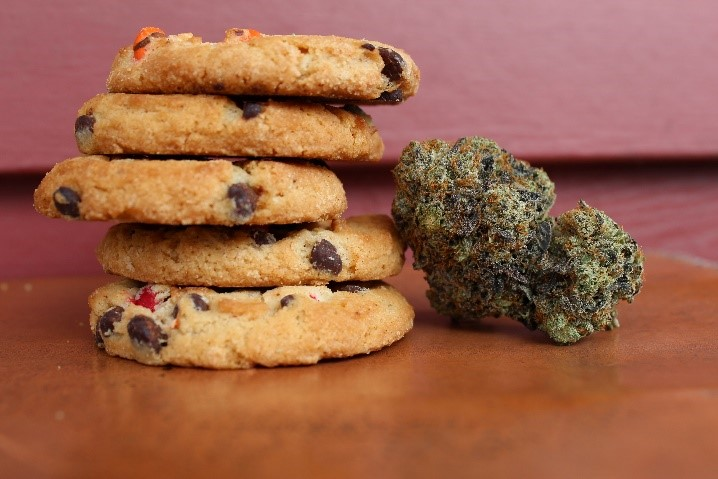 A stack of four cookies infused with marijuana next to some cannabis