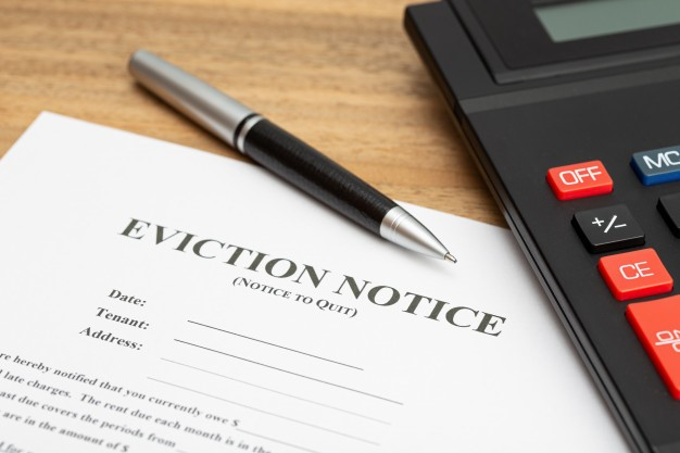 an eviction notice with a pen forcing a tenant to leave the house for using MMJ