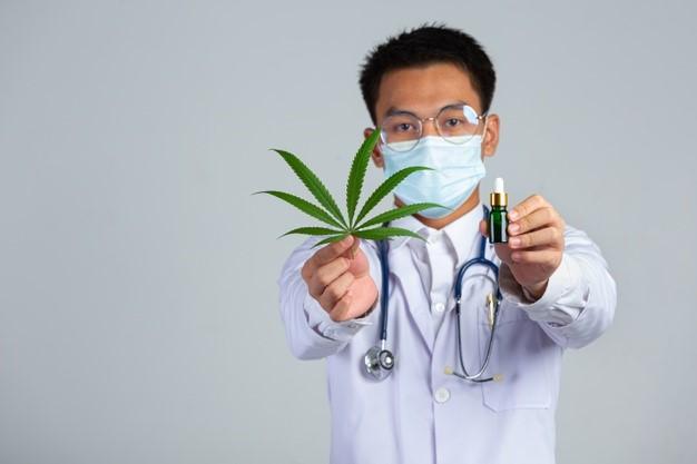 A medical marijuana doctor holding a cannabis leaf and oil.