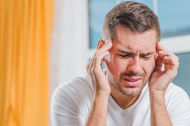a man with migraine holding his head with his hands and scrunching his forehead