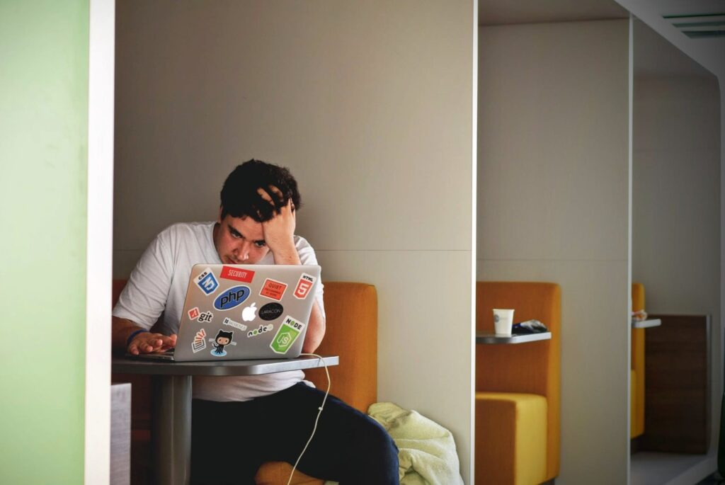 Man looking stressed working on laptop