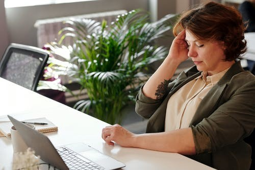 A woman suffering from a headache takes a break during work.