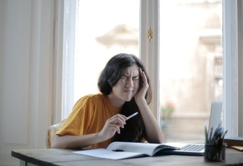 A young woman looks stressed as she struggles to concentrate with fibro-fog.