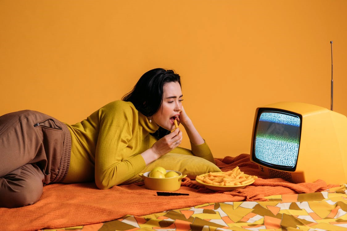 Woman eating and watching TV
