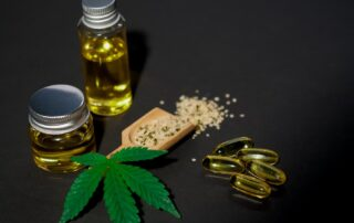 CBD Oil and marijuana leaves on a table.