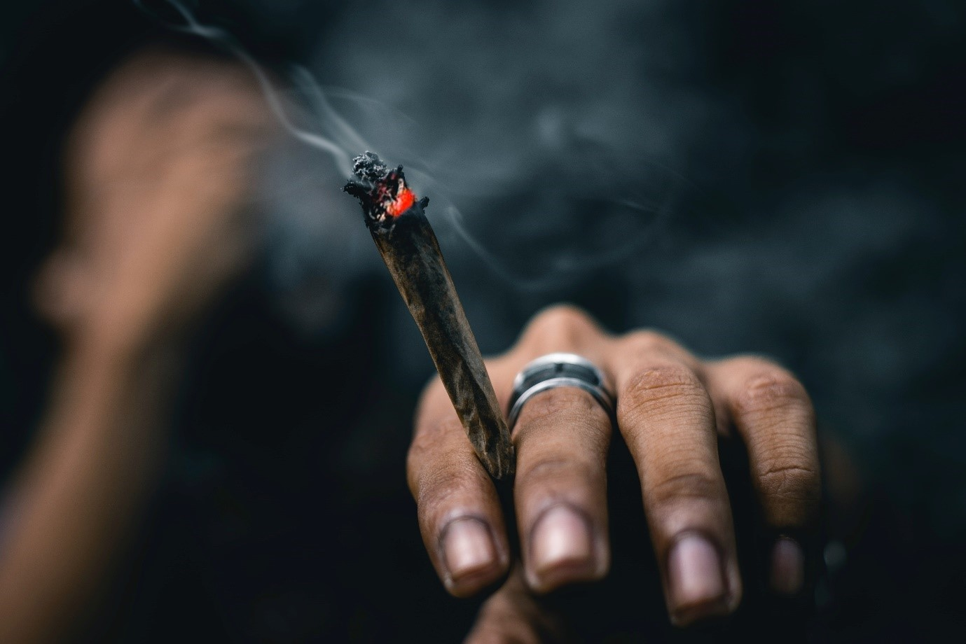A person holding a lit joint
