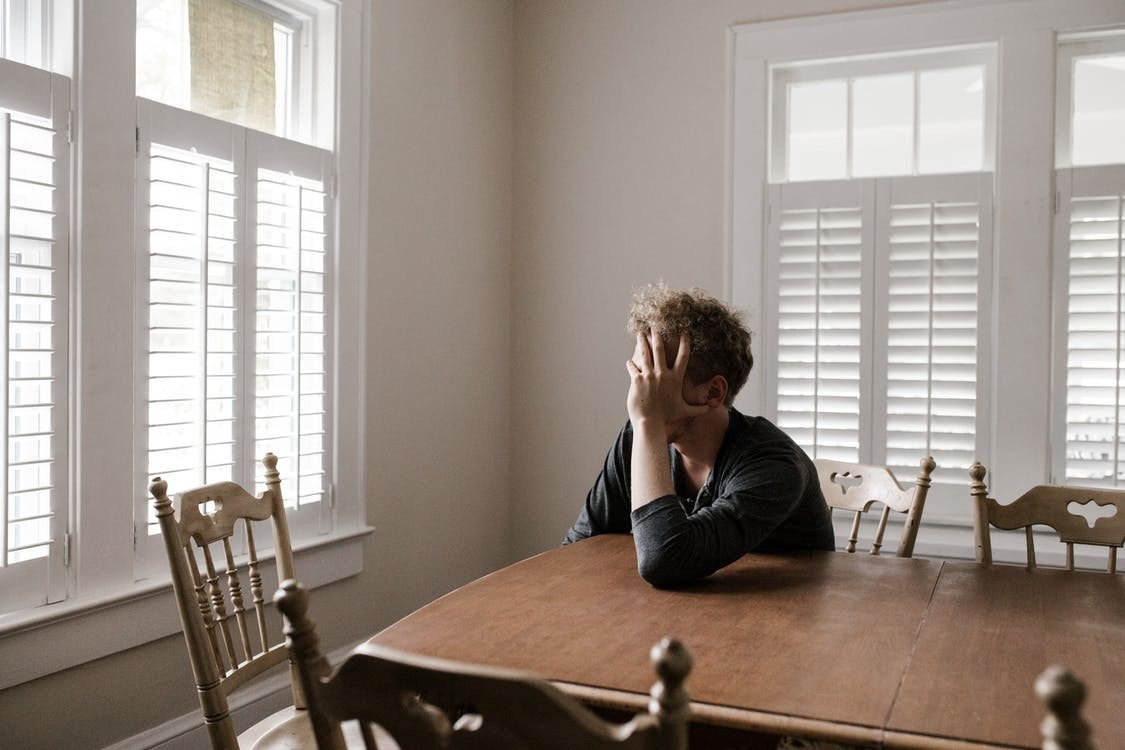A person struggling with aches and other health conditions sits at a table.